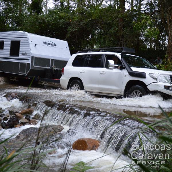 four wheel drive towing caravan through creek crossing