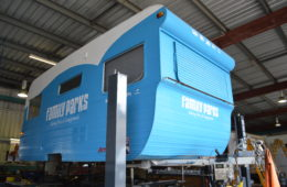 family parks caravan on hoist in workshop being repaired