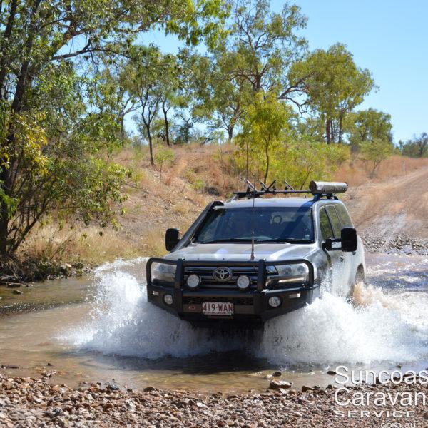 four wheel drive driving through creek crossing