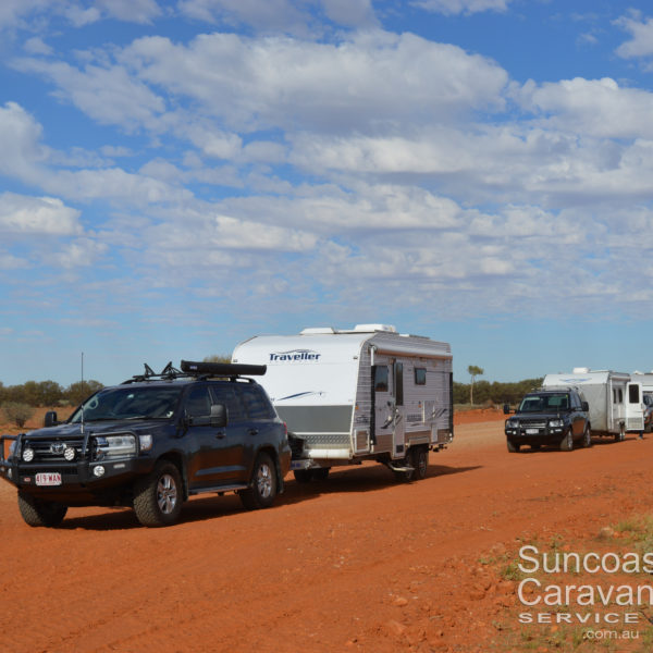 caravan convoy stopped on red dirt road in outback australia