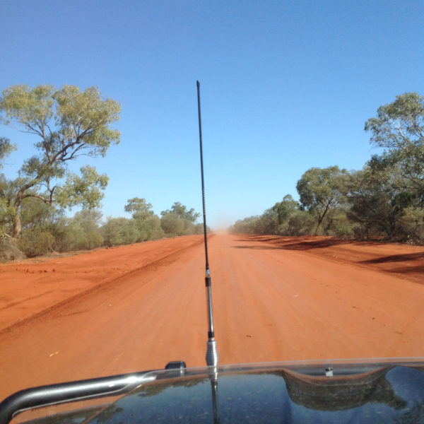 Looking through car windscreen to red dirt road in outback Australia
